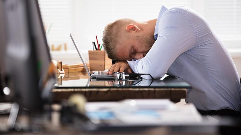 homme dort sur son lieu de travail